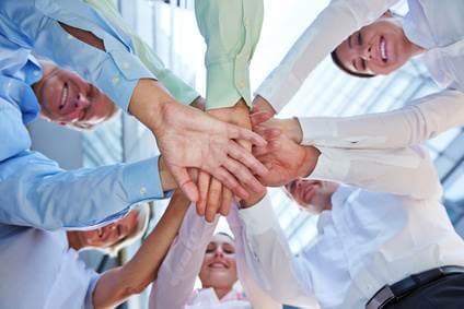 Business Team zeigt Verbindung und Zusammenhalt mit vielen gestapelten Händen
